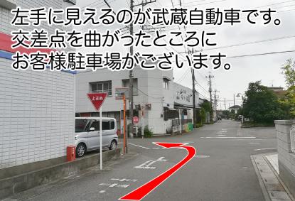 左手に見えるのが武蔵自動車です。交差点を曲がったところにお客様駐車場がございます。